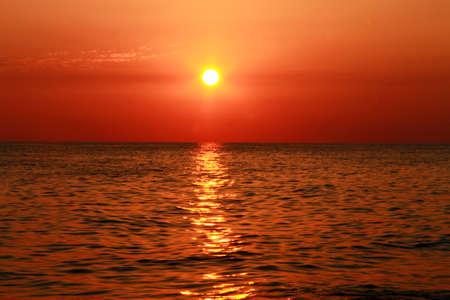 Summer sunset on the beach of the sea photo