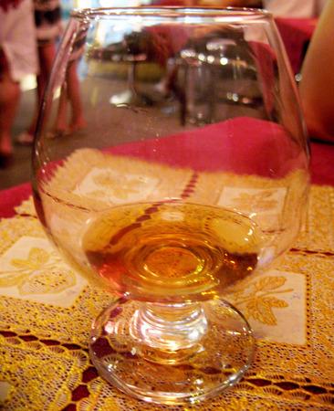 drunks: Half Empty Glass of cognac still on the table in restaurant