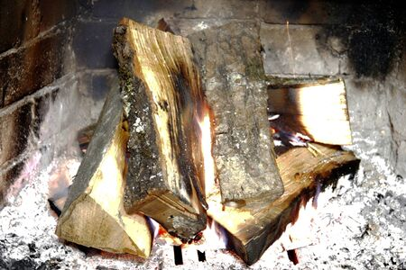 cosiness: Firewood in the fireplace burning in wintertime