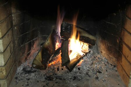 Firewood in the fireplace burning in wintertime