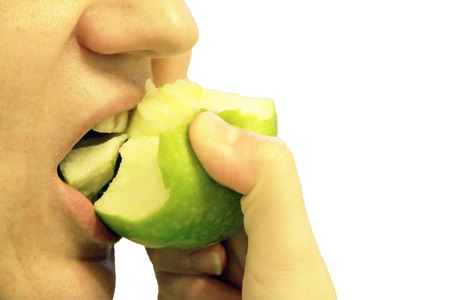Woman bit a green apple isolated on the white