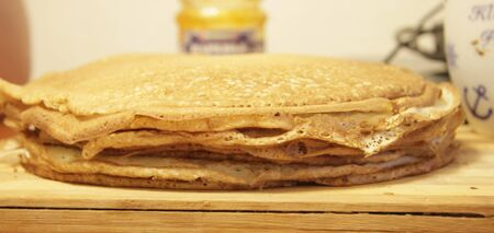 Stack of homemade pancakes on wood cooking board