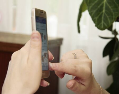 Womans hand hold smartphone and touch a screen