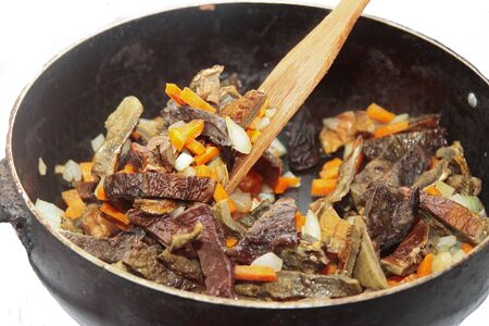Mushrooms fried on the pan with carrot and onion