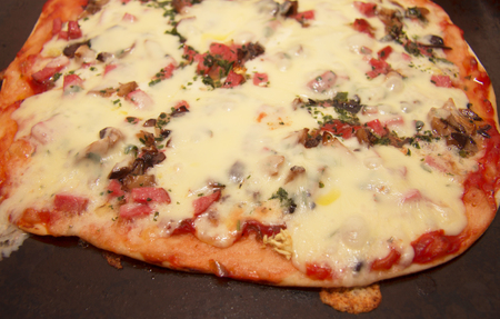 Hot pizza with mozzarella, fried mushrooms, sausage and parsley on the dripping pan Stock Photo