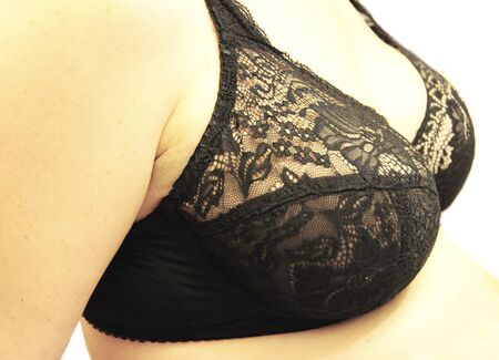 Woman breast in the black bra isolated on the white background