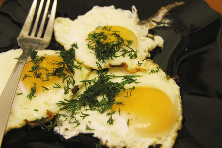 Fried eggs on the plate and dill over and fork near Stock Photo