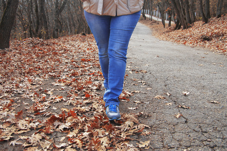 Young woman walking in autumn park close up