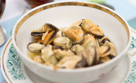 Tasty oiled pickled mussels iin the white plate on the table closeup Stock Photo