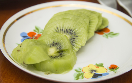 Fresh kiwi fruit sliced to pieces on the white plate on the brown wooden table