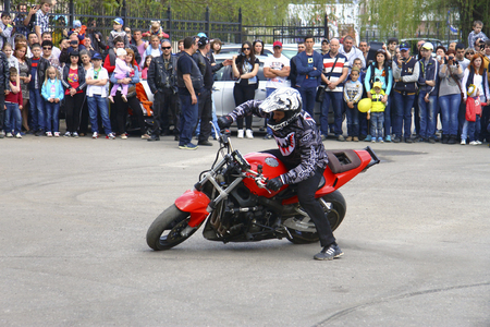 Moto free style pilot on the red motorcycle stunting on the square - Pyatigorsk Russia Opening of moto season 2015 on 1st May 2015 Editorial