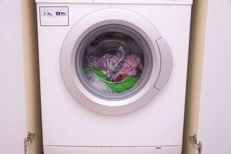 Front view of a washing machine drum during cleaning clothes inside built-in wardrobe Stock Photo