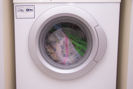 Front view of a washing machine drum during cleaning clothes inside built-in wardrobe 写真素材