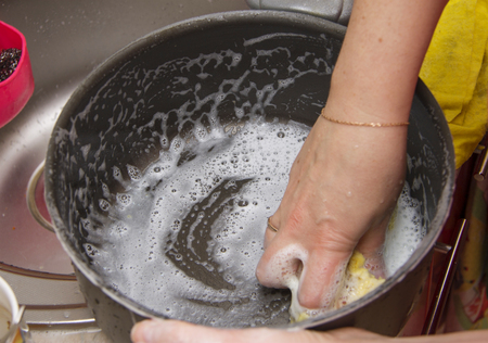 Woman washing the pan by hands in the sink in the kitchen under clean running water