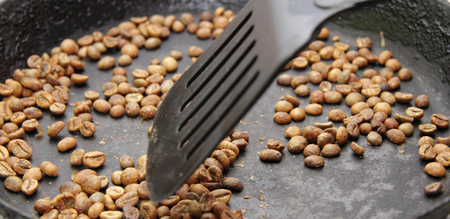 The green coffee beans roasting to black and stir up on the black pan Stock Photo