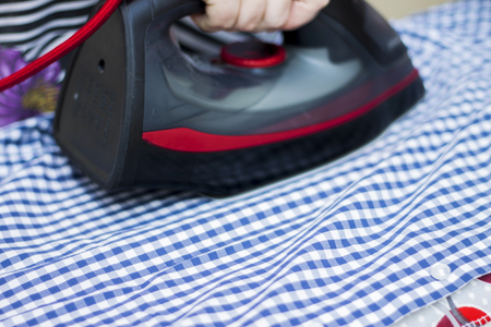 Housewife ironing a casual checkered clothes on the ironing board closeup