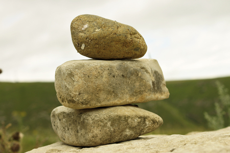 Three different Balanced stones on the alpine field near caucasus mountains Stock Photo