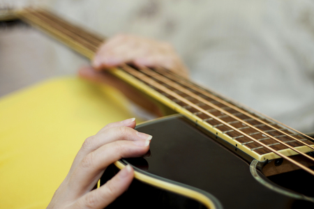 Female holding An acoustic bass guitar and ready to play music