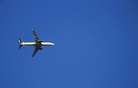 Airplane flying against blue sky. Clear blue sky background and flying machine foreground