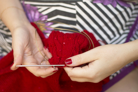 Adult woman knits with knitting needles a red sweater from natural woolen threads indoor