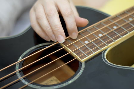 Female holding An acoustic bass guitar and play music Standard-Bild