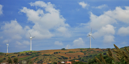 Wind power stations in the desert of Tunisia and landscape against cloudy sky