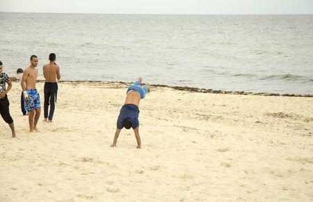 Acrobatics stunts on the sand. The beach of Sousse, Tunisia 04 october 2018 Reklamní fotografie