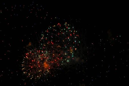 The Celebration multicolored firework flashing in the black night sky background
