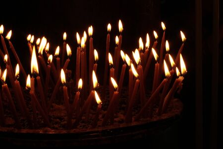 Some candles burn in the church in the darkness close up against black background Imagens