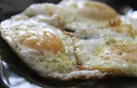 Morning roasted whole eggs on the black plate and dill over closeup