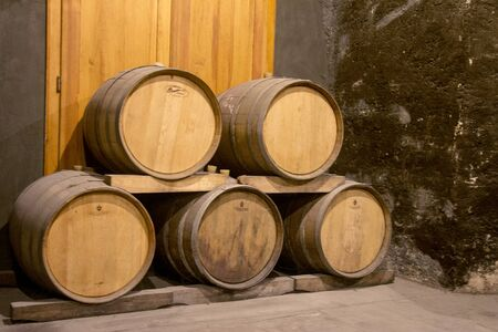Many Old wooden grunge barrels store in the wine cellar of monastery