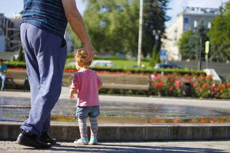 Father with baby near a splashing fontain in the center of town 12 June 2016 Pyatigorsk, Russia, Town Square Imagens