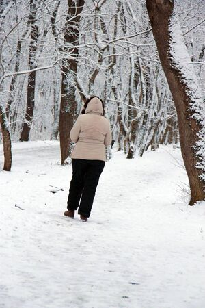 A Woman walk away alone in the winter park outdoor
