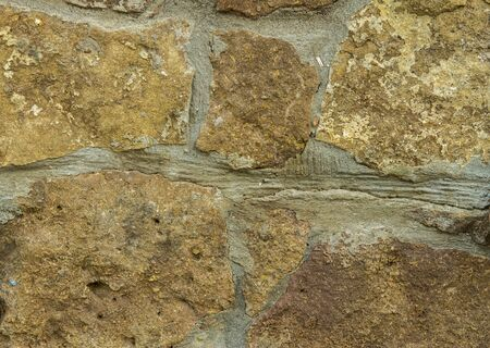 Yellow old grunge rough stone wall Stone Vintage Texture Background horisontal position Imagens