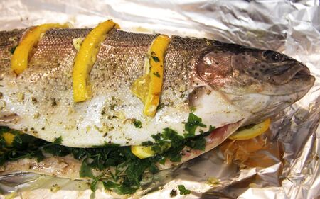 Trout fish filled by orange, herbs and spices and ready to cook in foil