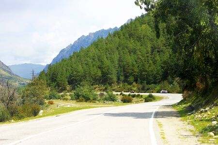 Mountain highway through the forest landscape. North Caucasus travel Imagens