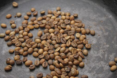 The green coffee beans roasting to black and stir up on the black pan Imagens