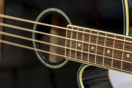 An acoustic bass guitar closeup isolated on the white background Imagens
