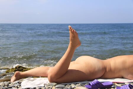 Beautiful adult naked woman have a sunburn on the seashore