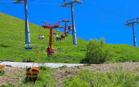 People on the double chairs of cableway. Dombai mountains, Russian Federation 10 june 2012