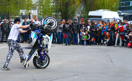 Moto free style pilot on the pink and green motorcycle stunting on the square - Pyatigorsk Russia Opening of moto season 2015 on 1st May 2015 Stock fotó - 158645318