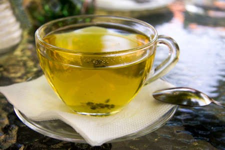 Cup of herbal tea in transparent cup outdoors and metal spoon near. Tea from herbs of highlands regions Banco de Imagens
