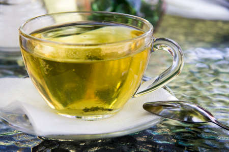A cup of herbal tea with a spoon on the table Stock fotó - 158244820