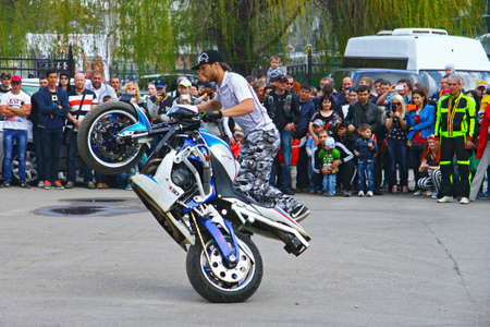 Moto free style pilot on the white and blue motorcycle stunting on the square - Pyatigorsk Russia Opening of moto season 2015 on 1st May 2015