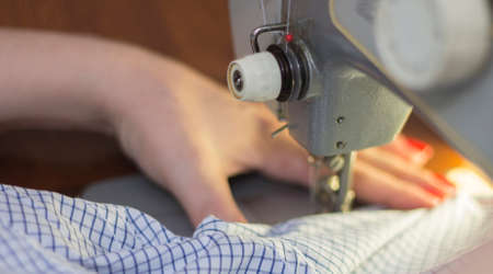 Woman taylor is working on the sewing machine closeup