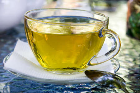 Cup of herbal tea in transparent cup outdoors and metal tea spoon near. Tea from herbs of highlands regions