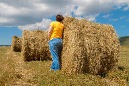 Woman near straw roll bales in harvested field at the daytime in the end of summer