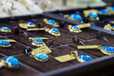 Jewelry hanging with blue stone on the shelf of jewerely store Turkey 27 september 2019