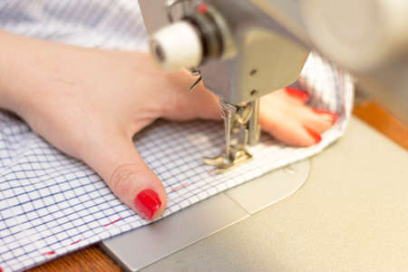 Woman taylor is working on the sewing machine closeup. Female with red nails sewing white chekered clothes