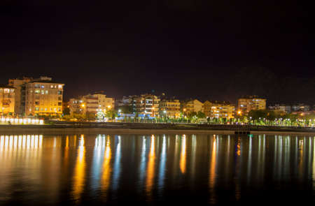 View of the illuminated night town line in Antalya Konyalti Turkey and river reflection at night time